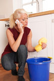 Woman Mopping Up Leaking Sink On Phone To Emergency Plumber Royalty Free Stock Images