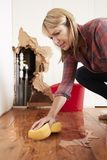Woman mopping up water from a burst pipe with sponge, vertical stock images