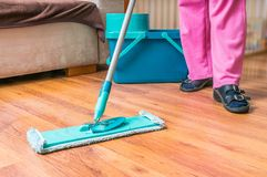 Woman is mopping wooden floor with mop.  Stock Images