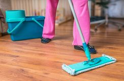 Woman is mopping wooden floor with mop.  Royalty Free Stock Photography