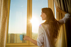 Woman in the morning. Attractive woman with neat body is ho. Lding a cup with hot tea or coffee and looking at the sunrise standing near the window in her home stock image