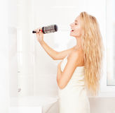 Woman in the morning at bathroom. Funny female sing song in comb Stock Photography