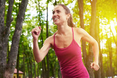 Woman on a morning run in the forest enjoying fresh air Stock Photo