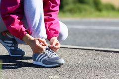 The woman on a morning run in a pink jacket and gray pants Royalty Free Stock Image