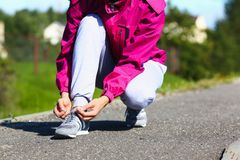 The woman on a morning run in a pink jacket and gray pants Stock Photography