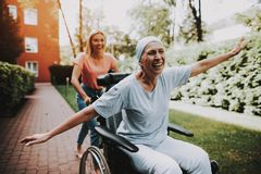 Woman with Mother. Cancer. Having Fun. Clinic. Patient Undergoes Rehabilitation. Cancer Patient on a Wheelchair. Woman with Daughter. Woman Glad See Daughter royalty free stock images