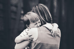 Woman mother comforting her crying little toddler boy son. Black and white portrait of young Caucasian women mother comforting her crying little toddler boy son stock photo