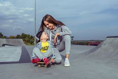 Woman mother encourages and motivates child on skateboard, little boy 3-5 years old, summer sports field in city, autumn
