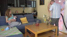 Woman mother hold sleep baby on hands. Man hoover home. 4K stock footage