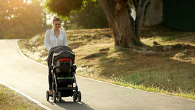Woman Mother Mom With Toddler in Pushchair Walking In Park Stock Images