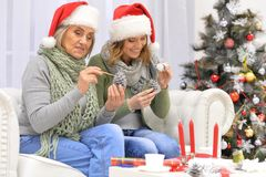 Woman and mother preparing to Christmas. Young women and her mother preparing to Christmas at home, sitting on sofa Royalty Free Stock Photo