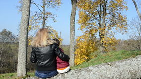 Woman mother sit cut tree trunk daughter admire autumn tree. Blond woman mother sit on cut tree trunk with her daughter admire autumn beautiful trees stock video footage
