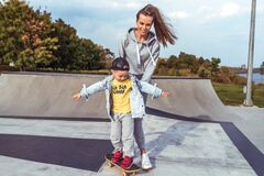Woman mother supports child, assistance learning, little boy 4-5 years old, learns ride skateboard, summer on sports