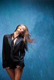 Woman in motion. Young woman in black tuxedo and tie with head in motion studio shot Royalty Free Stock Photos