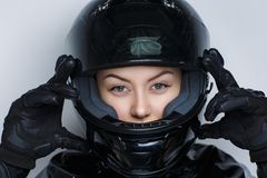 Woman moto helmet. Closeup portrait beautiful girl woman lady wearing moto helmet. Luxury black color leather material, magazine styling. Bright shiny shadows royalty free stock photography