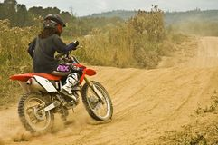 Woman motocross rider. Forty plus caucasian female learning to ride dirt bike on a dusty sand track stock photography