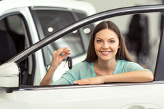 Woman in motor show. Beautiful young woman in casual clothes is smiling and showing car keys while leaning on a new car in a motor show Royalty Free Stock Photography