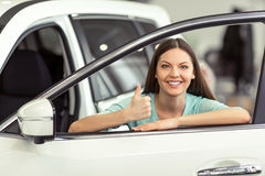Woman in motor show. Beautiful young woman in casual clothes is smiling and showing Ok sign while leaning on a new car in a motor show Royalty Free Stock Images