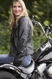 Woman and motorbike. Blond woman in leather next to motorbike royalty free stock photos
