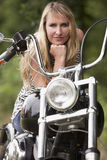 Woman and motorbike. Blond woman on a motorbike royalty free stock photos