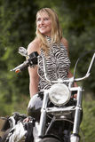 Woman and motorbike. Blond woman next to motorbike royalty free stock photography