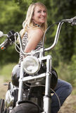 Woman and motorbike. Blond woman next to motorbike stock photo
