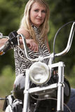 Woman and motorbike. Blond woman sitting on chopper motorbike stock photo