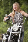 Woman and motorbike. Blond woman next to motorbike stock image