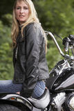 Woman and motorbike. Blond woman in leather next to motorbike royalty free stock photography