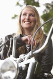 Woman and motorbike. Blond woman on a motorbike royalty free stock photography