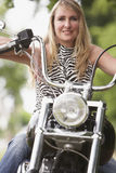 Woman and motorbike. Blond woman on a motorbike royalty free stock photo