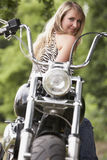 Woman and motorbike. Blond woman on a motorbike royalty free stock images