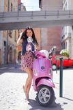 Woman and motorbike. Woman and pink motorbike on street Stock Photography