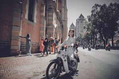 Woman on motorbike in city Stock Photos