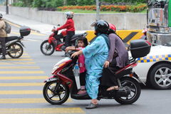 Woman on motorbike with her pillion riders. Woman on a motorcycle with her children as pillion riders on the road Royalty Free Stock Image