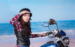 Woman on Motorcycle at Beach Looking into Distance Royalty Free Stock Images