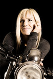 Woman on a motorcycle face lit in dark look up Stock Photo