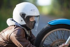 Woman in a motorcycle helmet clutching motorbike spoked wheel looks at a headlight Royalty Free Stock Photos