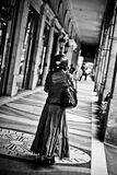 Woman with motorcycle helmet walk under a covered gallery Stock Images