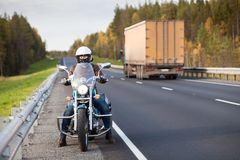 Woman on a motorcycle stands on the roadside of a country highway near passing freight truck Royalty Free Stock Photos