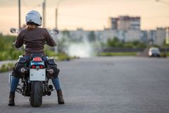 Woman a motorcyclist ready to stard riding on motorbike on asphalt road, copy-space Stock Photography