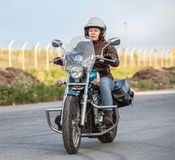 Woman motorcyclist riding solo on chopper on asphalt urban road Royalty Free Stock Images