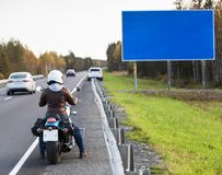 Woman motorcyclist standing on the asphalt road in front of the blank information board with blue background, autumn season Royalty Free Stock Images