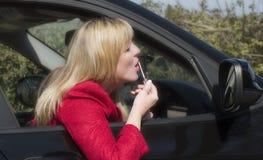 Woman motorist applying makeup Stock Photography