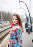 Woman at mottled suit waiting delayed train Royalty Free Stock Photos