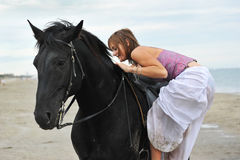 Woman mount a  horse on the beach. Beautiful black  horse on the beach and beautiful woman mount it Stock Photo