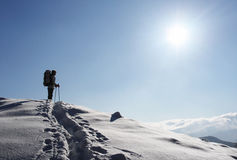 Woman is in mountain. Backpacker moving up in winter mountain under blue sky Stock Images