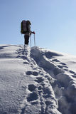 Woman is in mountain. Backpacker moving up in winter mountain under blue sky Royalty Free Stock Image