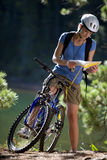Woman on mountain bike looking at map Stock Photo