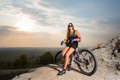 Woman with the mountain bike under a sky at sunset Stock Image